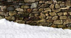 Pared de piedra en nieve Foto de archivo libre de regalías