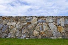Pared de piedra en un césped y un cielo azul Foto de archivo