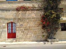 Pared de piedra de la puerta roja imagen de archivo