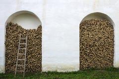 Pared de piedra, leña y escalera de madera Fotos de archivo