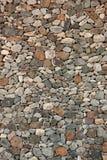 Pared de piedra natural canaria con las piedras multicoloras Fotos de archivo