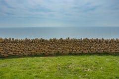Pared de piedra que separa el prado verde del horizonte Imagenes de archivo