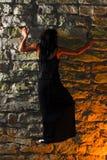 Pared de piedra que sube de la mujer de Goth Fotografía de archivo libre de regalías