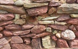 Pared de piedra seca con la estructura tradicional de las piedras rojas y rosadas sin el mortero Imágenes de archivo libres de regalías
