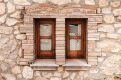 Pared de piedra vieja con dos pequeñas ventanas en marcos de madera Fotografía de archivo libre de regalías