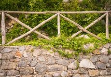 Pared de piedra vieja con la cerca de madera en ella fotos de archivo