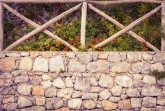 Pared de piedra vieja con la cerca de madera en ella imagen de archivo