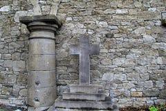Pared de piedra vieja con la cruz del cementerio y columna que descansa contra ella Imágenes de archivo libres de regalías
