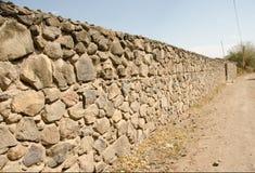 Pared de piedra y camino de tierra Fotos de archivo libres de regalías