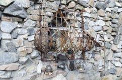 Pared de piedra y parrilla oxidada vieja del metal en la ventana Foto de archivo