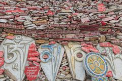Pared de piedras de Mani en la pared de Mani Temple Mani Shicheng con el mantra budista OM Mani Padme Hum grabado en tibetano en  Imagen de archivo libre de regalías