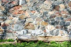 Pared de piedras naturales grandes y de alguna hierba verde foto de archivo