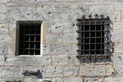 Pared de un castillo con la ventana barrada Imágenes de archivo libres de regalías