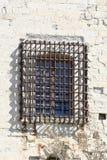 Pared de un castillo con la ventana barrada Fotos de archivo