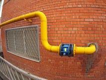 Pared de un edificio con un tubo de gas y una válvula grande Fotografía de archivo libre de regalías