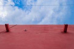 Pared de una casa rosada, en un cielo azul foto de archivo