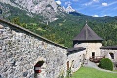 Pared del castillo Hohenwerfen, Austria, llevando abajo de una cuesta hacia una atalaya con los picos de la gama de Tennen en el  Imagen de archivo