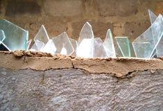 Pared del cemento cubierta con los pedazos de cristal quebrados Imagen de archivo libre de regalías