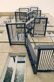 Pared del edificio con las escaleras y las ventanas de la emergencia vistas de debajo contra el retro del cielo filtrado Imagen de archivo libre de regalías