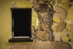 Pared destruida amarilla y ventana quebrada negra imagenes de archivo