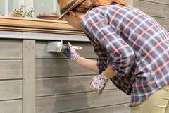 Pared exterior de la casa de madera de la pintura del trabajador de mujer con la brocha y el color protector de madera imagen de archivo