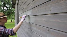 Pared exterior de la casa de madera de la pintura del trabajador de mujer con la brocha y el color protector de madera almacen de video