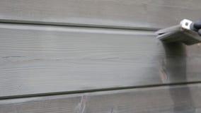 Pared exterior de la casa de madera de la pintura del trabajador de mujer con la brocha y el color protector de madera almacen de metraje de vídeo