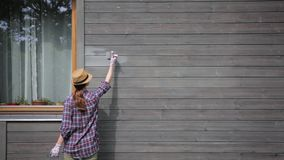 Pared exterior de la casa de madera de la pintura del trabajador de mujer con la brocha y el color protector de madera metrajes