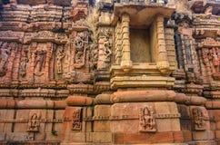 Pared exterior de las ruinas del templo y escultura de piedra maravillosamente tallada de la religión hindú y Jain fotos de archivo libres de regalías