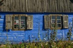 Pared externa de madera azul de una casa de campo con dos Fotografía de archivo