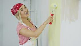 Pared femenina sonriente de la pintura con el rodillo almacen de metraje de vídeo