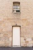 Pared grande de la piedra arenisca con la puerta blanca Foto de archivo libre de regalías