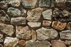 Pared hecha de las piedras ásperas que forman un fondo singular imagenes de archivo
