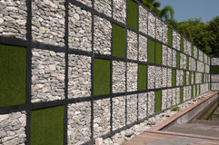 Pared hecha de roca y de hierba artificial fotografía de archivo