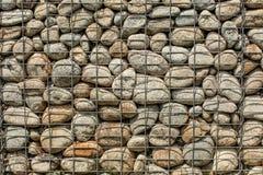 Pared hecha de rocas redondas, asegurado con el ston del hierro de la red de alambre de acero imágenes de archivo libres de regalías