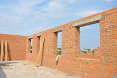 Pared inacabada de la casa del ladrillo rojo bajo construcción sin cubrir Construcción concreta del marco del dintel de Windows d Fotografía de archivo libre de regalías