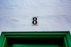 Pared negra de cerámica del blanco del número 8 sobre puerta verde Imagen de archivo libre de regalías