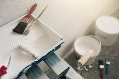 Pared preparada para pintar Cepillos, cubos de pintura, escaleras cerca de la pared fotografía de archivo