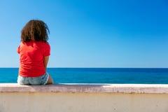 Pared que se sienta del adolescente de la muchacha de la mujer joven que mira al mar fotografía de archivo