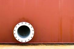 Pared roja, tubo del metal en la pared Imagen de archivo libre de regalías