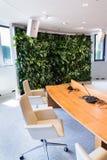 Pared verde viva, jardín vertical dentro con las flores y plantas bajo iluminación artificial en la sala de reunión de la reunión imagen de archivo