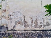 Pared vieja con yeso y adoquines blancos que desmenuzan en un patio Imagenes de archivo