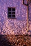 Pared violeta con tres ventanas Imagen de archivo libre de regalías