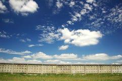 Pared y cielo azul con las nubes Foto de archivo