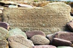 Pared y piedras de Mani con símbolos budistas Fotos de archivo