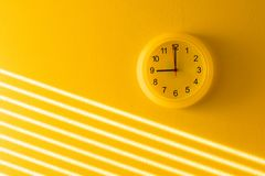Pared y reloj amarillos Imagenes de archivo