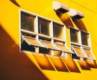 Parede amarela com quadro de janela de vidro sombra através do fundo de vidro do conceito da construção do verão fotografia de stock