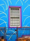 Parede azul da casa com janela roxa Patamar com wicket Imagem de Stock Royalty Free