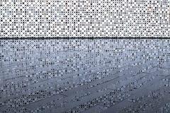 Parede branca perfurada e sua reflexão na telha molhada após a chuva foto de stock