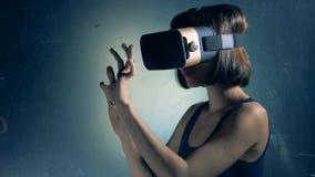Parede com informação projetada e uma menina nos VR-vidros que estão ao lado dela video estoque
